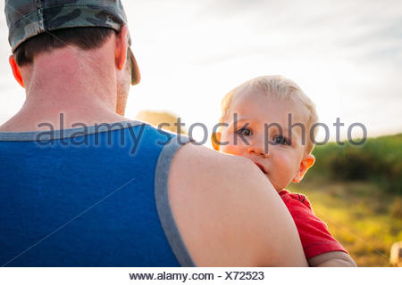 Father carrying his son on his shoulder - Stock Photo