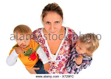 nerved mother with her children on her arms, girl eating a biscuit, boy picking his nose - Stock Photo