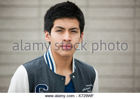 Young man wearing baseball jacket, portrait - Stock Photo