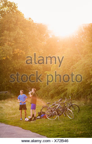 Sporty male friends standing by bicycles at park during sunset - Stock Photo