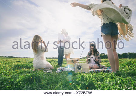 Five young adult friends having a picnic in field - Stock Photo