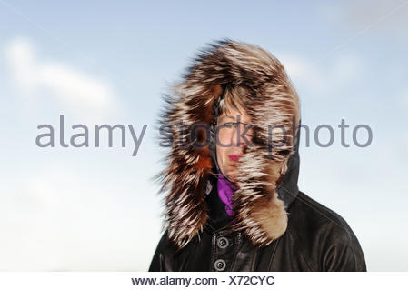Portrait of a woman with fur hood occupied in the - Stock Photo