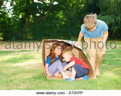 Siblings hiding in cardboard box in garden - Stock Photo