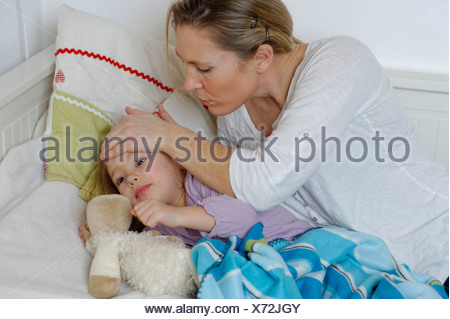Mother taking care of her sick daughter, child lying in bed - Stock Photo