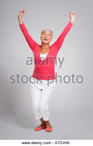 Older lady throwing up her arms in joy - Stock Photo