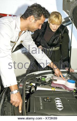 Autowerkstatt Mechaniker Kundin Kundendienst, Beratung erklaeren Wartung Werkstatt Mann Frau Kundenbetreuung Arbeiter Auto Fahrz - Stock Photo