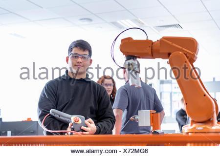 Portrait of robotics apprentice using test industrial robots in robotics facility - Stock Photo
