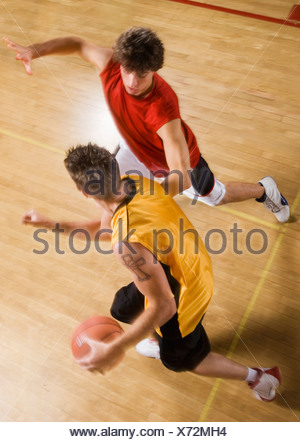 Two young men playing basketball on indoor court - Stock Photo