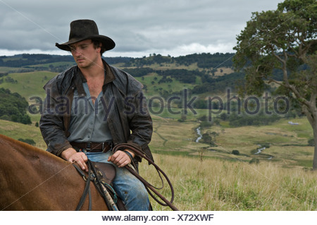 Man on horse in countrside - Stock Photo