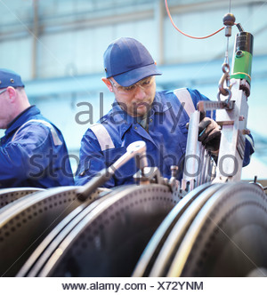 Engineers fitting blades to steam turbine in repair works - Stock Photo