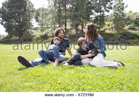 Family with two boys and dog sitting in park