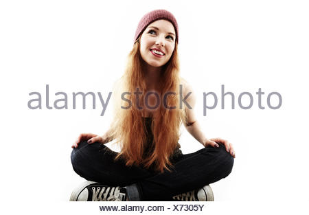 Studio portrait of young woman sitting cross legged on floor - Stock Photo