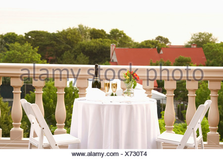 Champagne bottle and two champagne flutes on the table - Stock Photo