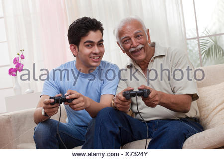 Grandfather and grandson playing video game - Stock Photo