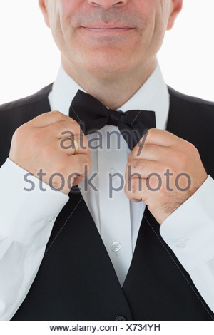 Waiter adjusting his bow tie - Stock Photo