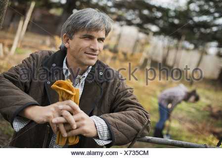 A man in a brown jacket holding leather work gloves on an organic farm A person digging in the ground with a spade - Stock Photo