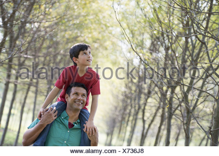 A boy having a piggyback riding on a man's shoulders. - Stock Photo