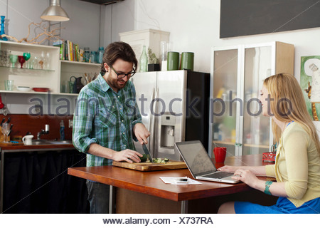 Woman on laptop computer, man chopping vegetables - Stock Photo