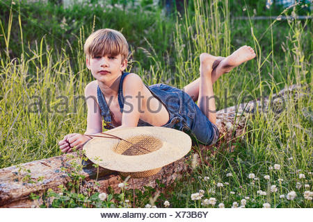 Young boy wearing blue overalls laying on fallen tree - Stock Photo