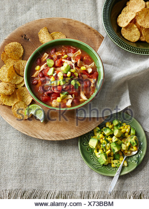 Plates of chicken soup and avocado - Stock Photo