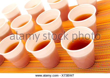 Lots of disposable cups with tea on a colorful background - Stock Photo