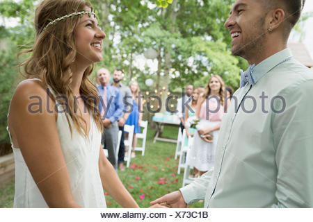 Bride and groom holding hands at backyard wedding - Stock Photo