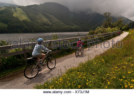 Mom and son biking along the Franconia Notch Bike Trail. - Stock Photo