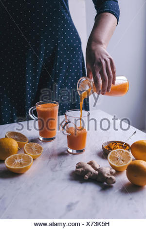 Woman pouring orange, lemon and carrot juice with turmeric and ginger into a glass - Stock Photo