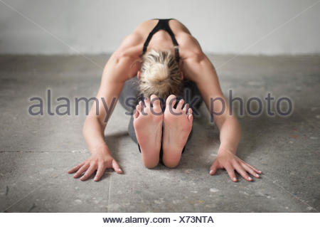 Mid adult woman practicing seated forward bend pose in yoga studio, Munich, Bavaria, Germany - Stock Photo