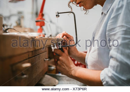 Cropped view of female jeweller using coping saw at workbench - Stock Photo