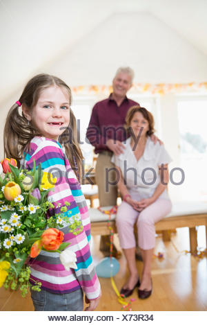 Granddaughter handover bouquet to her grandmother and grandfather in background - Stock Photo