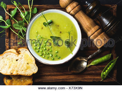 Fresh homemade pea cream soup in white bowl with grilled bread on wooden board over black backdrop, top view, horizontal composi - Stock Photo