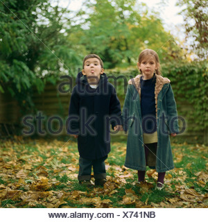 Girl and boy holding hands outside, boy sticking out tongue - Stock Photo