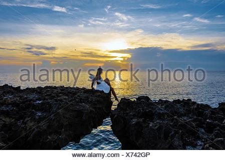 Woman Sitting On Cliff Over Sea Against Sky During Sunset - Stock Photo