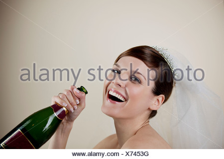 A young bride holding a bottle of champagne - Stock Photo