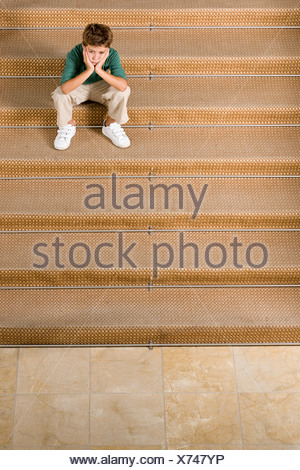 Bored boy sitting on stairs - Stock Photo