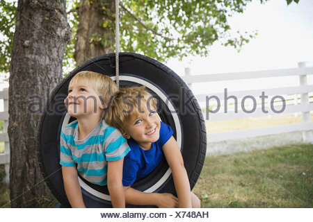 Playful boys on a tire swing - Stock Photo