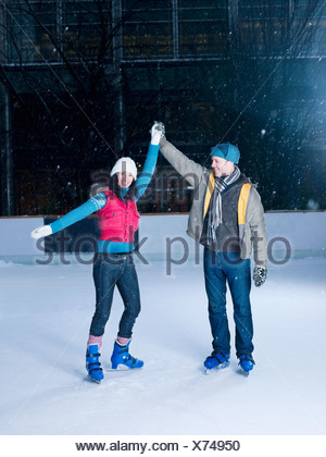 Couple holding hands on an ice rink - Stock Photo