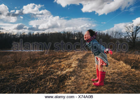 Girl with arms outstretched  shouting into the wind - Stock Photo