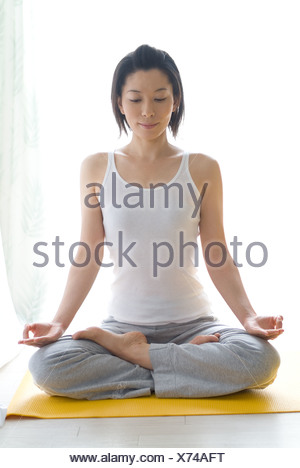 A mid adult woman sitting in lotus position - Stock Photo