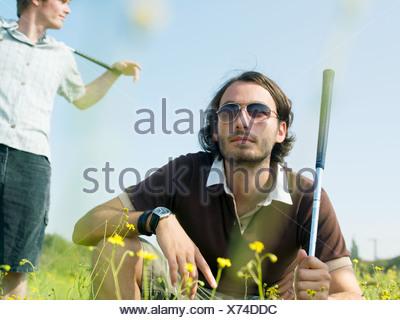 Male golfers in a field - Stock Photo