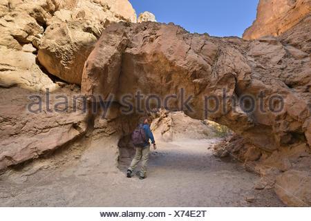 USA, California, Anza-Borrego Desert State Park, Hiker Walking underneath a Natural Bridge - Stock Photo