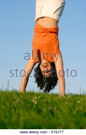 Young woman doing handstand on meadow - Stock Photo