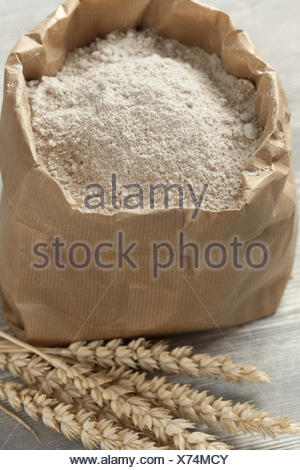 Dried wheat and wheat flour in a paper bag. - Stock Photo