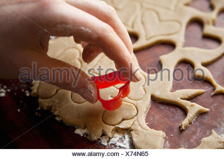Detail of a hand using a heart shape cookie cutter - Stock Photo
