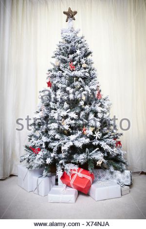 Decorated Christmas tree with gifts - Stock Photo