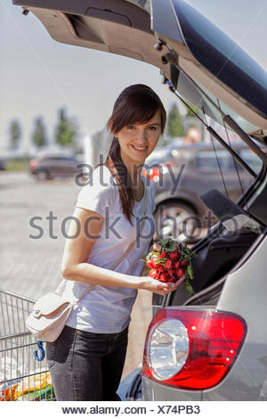 Portrait of smiling young woman loading purchase in her car - Stock Photo