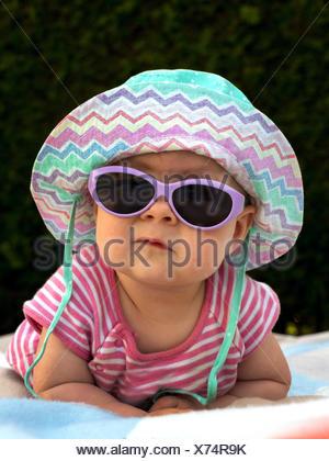 Baby mit Sonnenhut und Sonnenbrille in der Sommerhitze, Oesterreich   baby with sun hat and sun glasses in the summer heat, Aust - Stock Photo