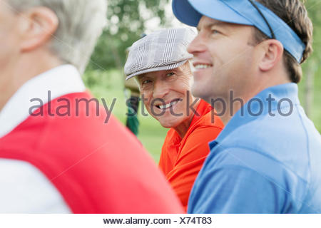 three golfers watching from bench on golf course - Stock Photo