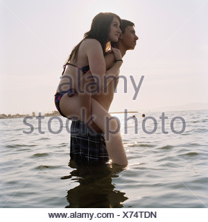 A young man giving his girlfriend a piggyback ride in the sea - Stock Photo